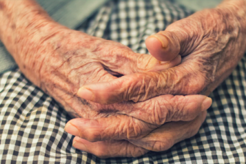 Close up image of an elderly woman's hands clasped on her knees