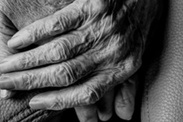 Close up of one elderly person's hands holding another hand