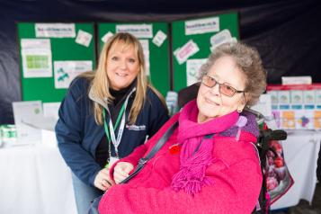 Healthwatch Volunteer at a community event speaking to a woman in a wheelchair