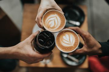 closeup of three hands holding cups of coffee