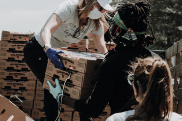 Volunteers offloading food parcels from the back of a truck