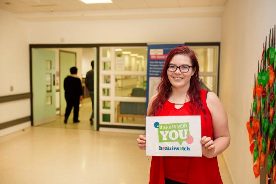 """Image of volunteer in a hospital holding a sign """"It starts with you"""""""