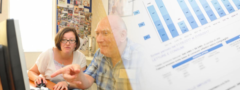A female carer showing an elderly man a website on a computer