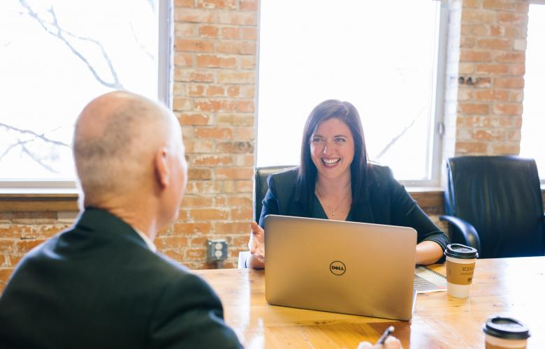 man sat across interview table from female interviewer with laptop