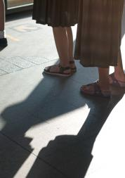 Peoples feet as they stand outside in a queue