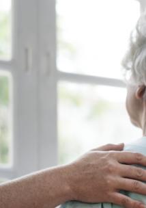 An elderly female patient talking to a nurse, overlooking a hospital window